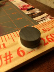 Glue a stack of two magnets on the yardstick with wood glue.